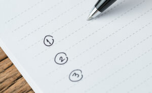 To-do list or writing tasks priority concept, close-up of list on numbers with pen and headline as To Do List on white paper notepad on wood table.